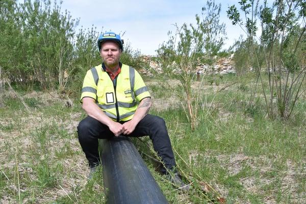 Anleggsleder Roger Trøsviken sittende på den spesialkonstruerte drensledningen SDR 4,5 - med 12 mm borede hull jevnt fordelt i hele rørets lengde.