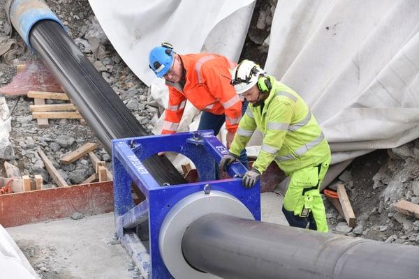 PE100-ledningen er trukket gjennom trakta og komprimmert med 10-12 prosent, konstaterer John Tore Madsen og prosjektleder VA i Kongsberg kommune, Jostein Dalshagen.