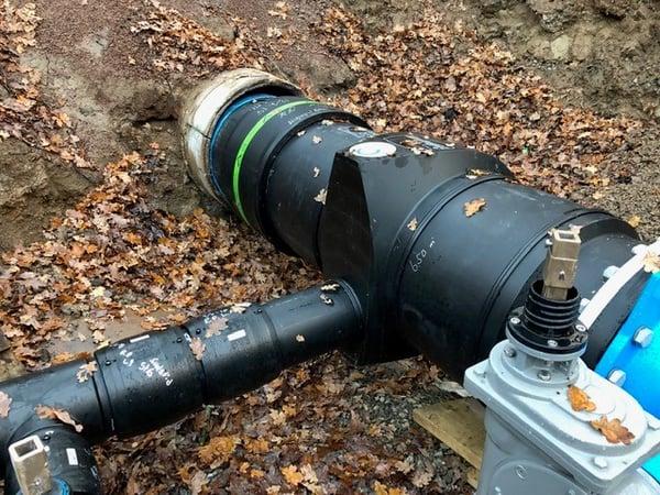 Innsveising av T-rør med flenset ventil i en trang trekkegrop under ett reliningsprosjekt.